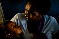 A child suffering from fever waits to be examined by a doctor - Horiara, Solomon Islands.